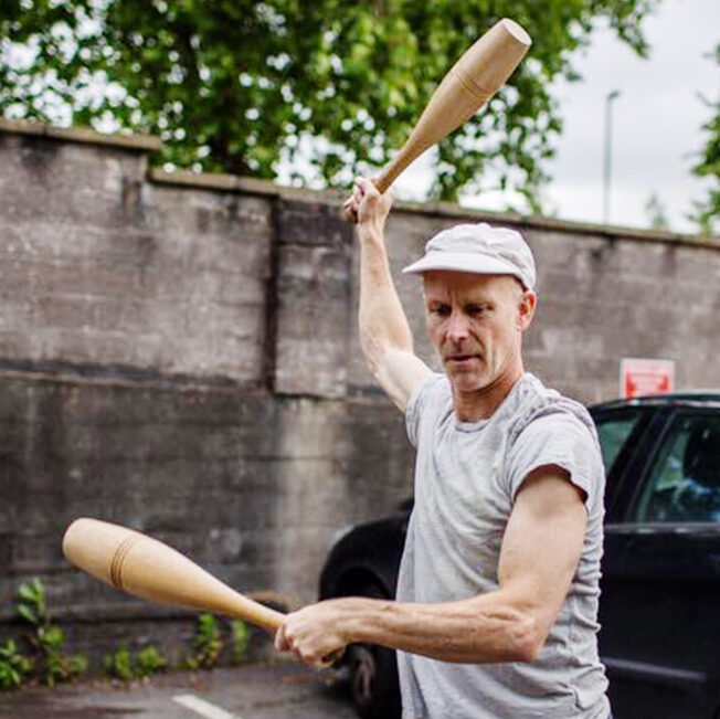 A person staging holding a wooden club in each hand, one is raised above the head and the other is held out in front of their body